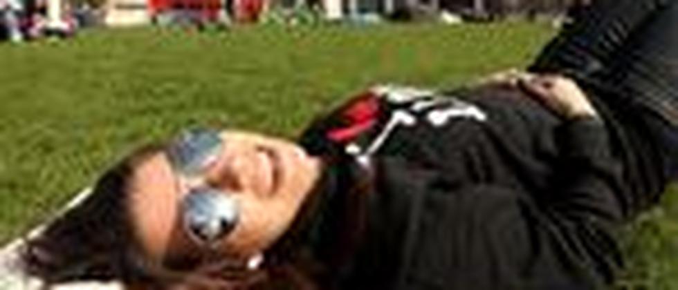 Ein Touristin liegt im Park in London