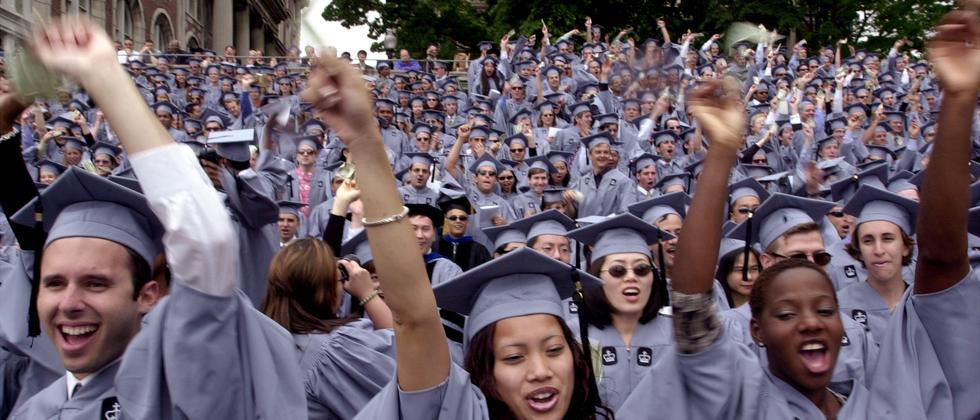 College-Studenten feiern in grauen Roben ihren Abschluss in New York City