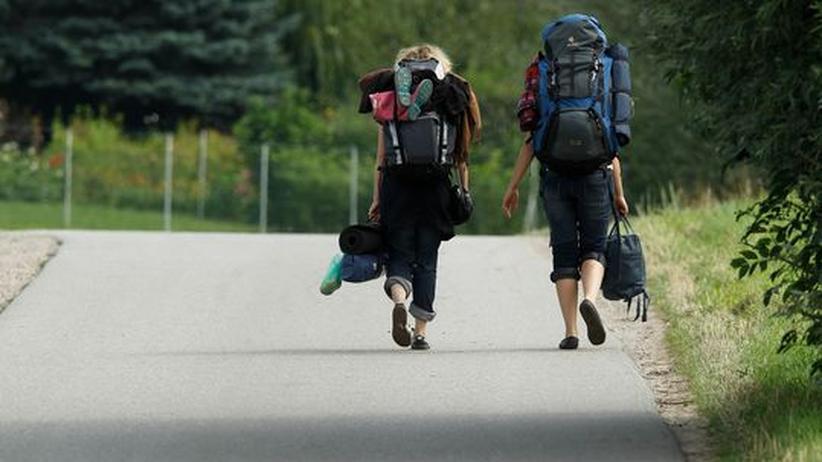 Zwei Backpacker laufen auf einer Straße