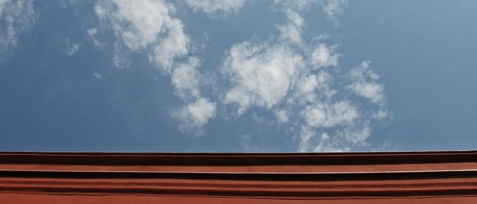 Eine Hausfassade mit der Aufschrift Uni, darüber ein Himmel mit Wolken