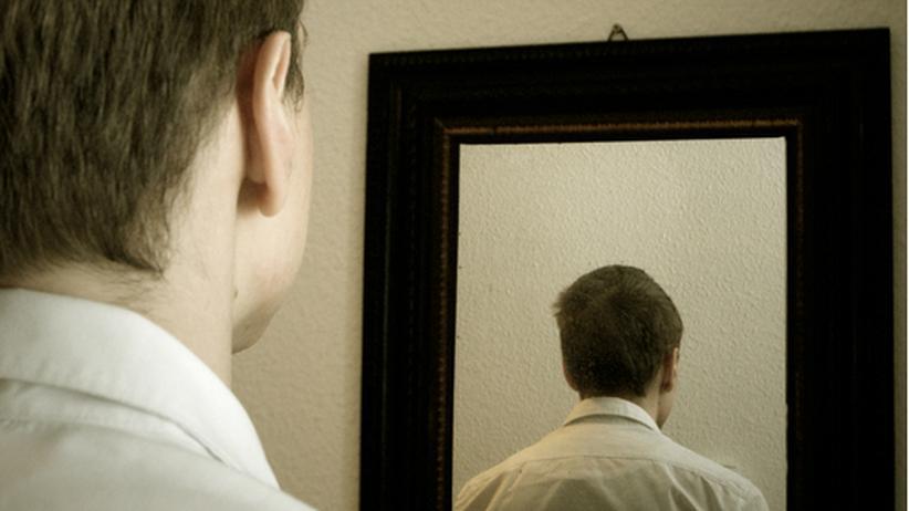 Mann sieht sich im Spiegel von hinten