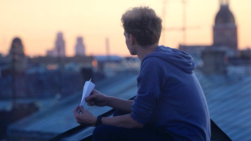 Jugendlicher sitzt auf Dachterasse und blickt über die Stadt.
