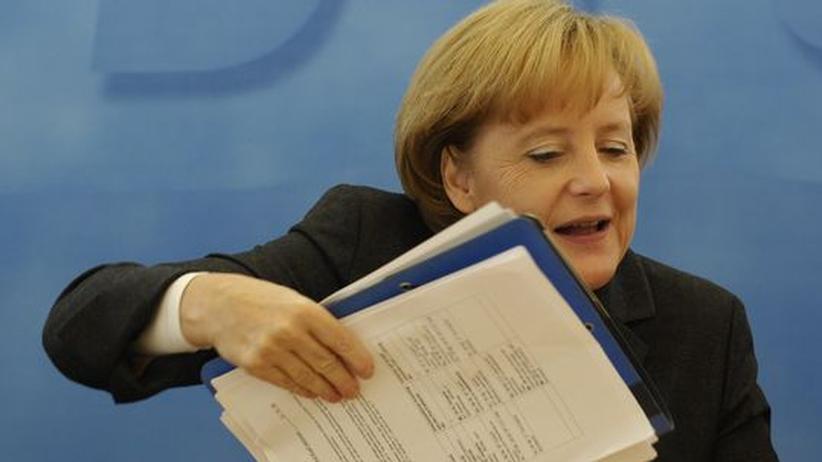 Bundeskanzlerin Angela Merkel mit einem Stapel Papiere. Wie viele davon kommen wohl von Lobbyisten?