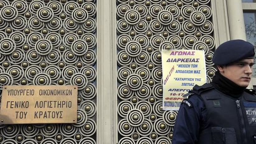 Ein Polizist bewacht die Tür einer Behörde in der Athener Innenstadt. Direkt neben ihm ist ein Flugblatt angeschlagen, dass einen Streik der Angestellten ankündigt