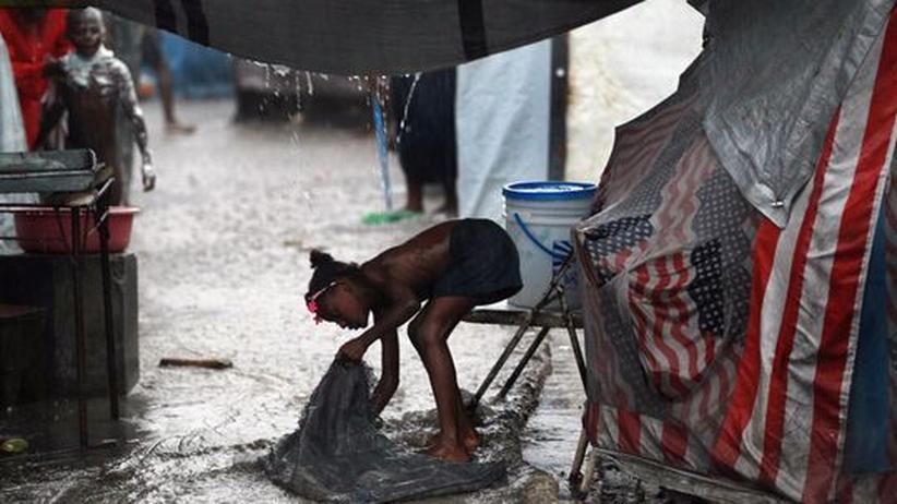 Ein Mädchen wäscht einen Sack im Regen aus