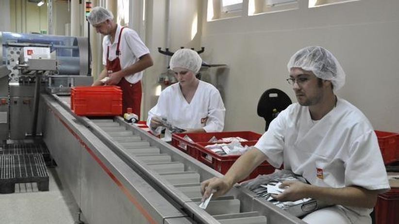 Drei Mitarbeiter sortieren die Zutaten für eine Backmischung aufs Band