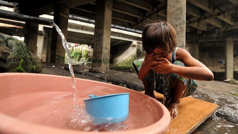 Ein Kind wäscht sich unter einer Brücke in Manila, der Hauptstadt der Philippinen