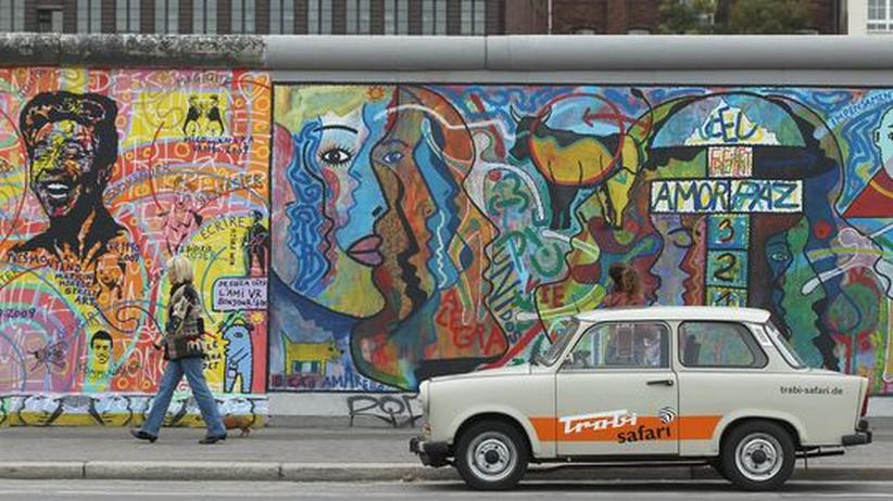 ein Trabant vor Überresten der Berliner Mauer, der sogenannten East Side Gallery