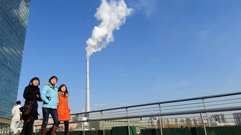 Energie: Fußgänger vor einem Kohlekraftwerk in Peking. China gewinnt einen großen Teil seiner Energie aus Kohle, fördert aber auch alternative Energien stark
