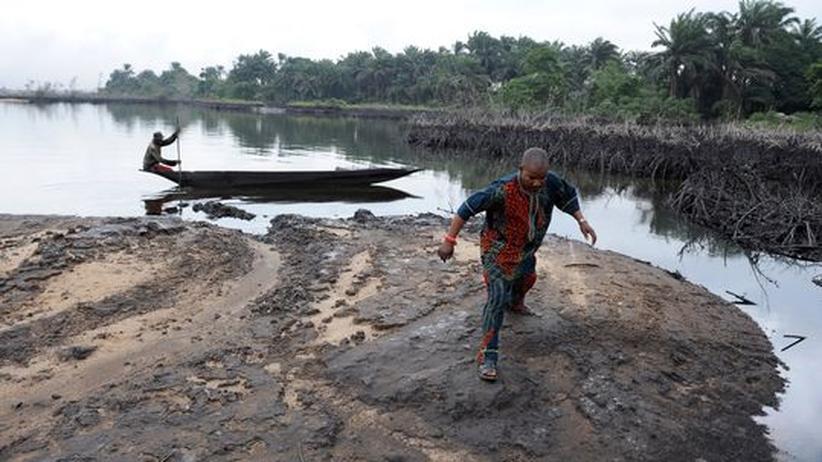 Ein Mann watet durch den Öl-Schlick am Ufer des Nigerdeltas