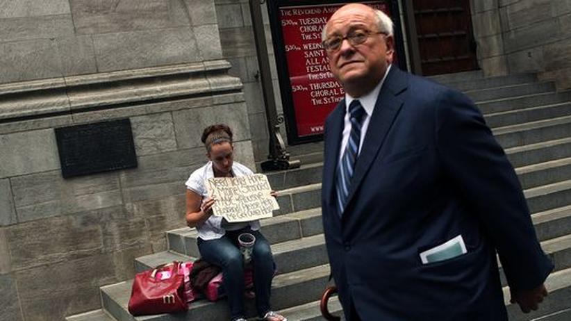 Straßenszene in New York: Ein Geschäftsmann geht an einer obdachlosen Frau vorbei
