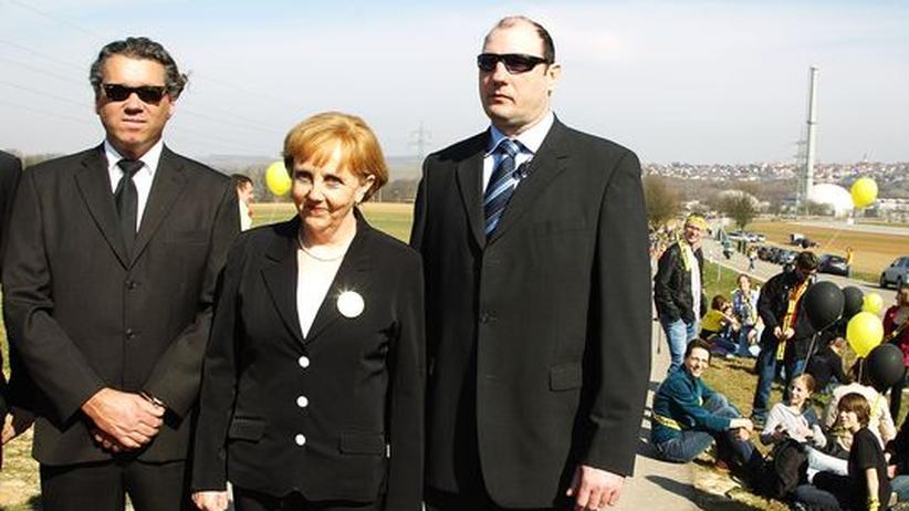 Kernkraft: Ein Double von Kanzlerin Angela Merkel mit Bodyguards posiert vor dem AKW Neckarwestheim. Die falsche Kanzlerin war Teil der Anti-Atomkraft-Demonstration vom 12. März.