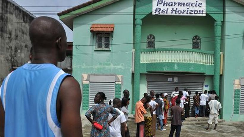 Entwicklungshilfe: Einheimische warten vor einer Apotheke in Abidjan, Elfenbeinküste