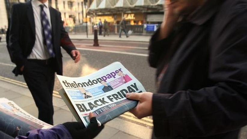 """Finanzkrise: Ein Zeitungsverkäufer in London verteilt am 10. Oktober 2008 Zeitungen an Passanten. Am """"Schwarzen Freitag"""" hatte die Börse in London schwere Kurseinbrüche erlebt."""