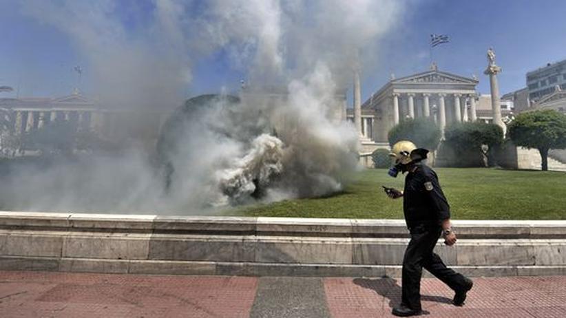 Schuldenerlass: Der Sparkurs der griechischen Regierung ruft im Land heftige Proteste hervor: Ein Feuerwehrmann geht an der Athener Universität vorbei, während in der Nähe Polizei und Demonstranten mit Gewalt aufeinander treffen (Aufnahme vom 11. Mai).