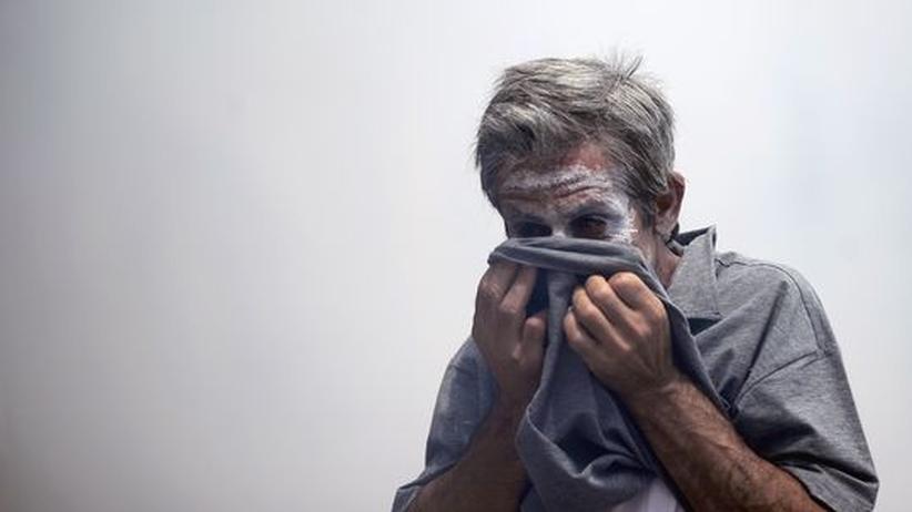 Euro-Gipfel: Vor wenigen Wochen in Athen: Ein Demonstrant schützt sein Gesicht vor Tränengas.