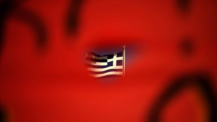 Euro-Krise: Die griechische Fahne auf dem Dach des Athener Parlaments, gesehen durch ein rotes Spruchband auf einer Demonstration Ende Juni