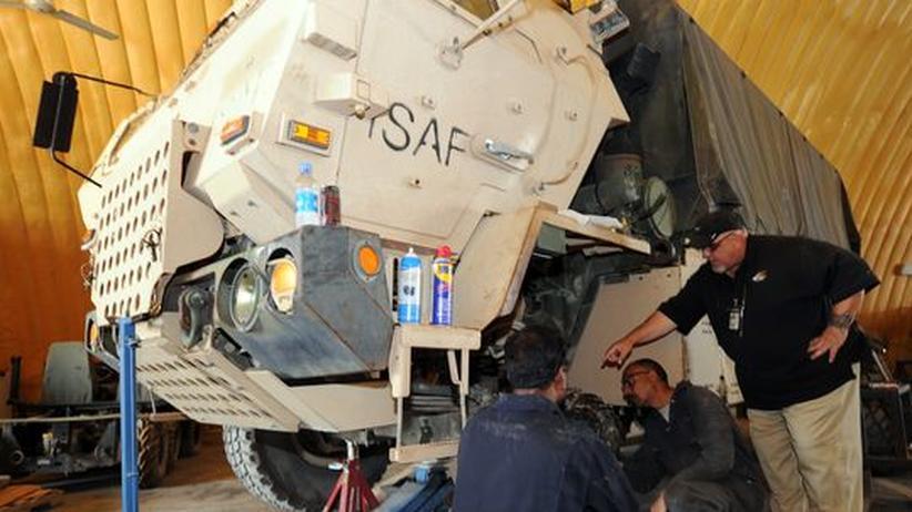 Mitarbeiter eines privaten Dienstleisters reparieren für die US-Armee Fahrzeuge in Afghanistan.