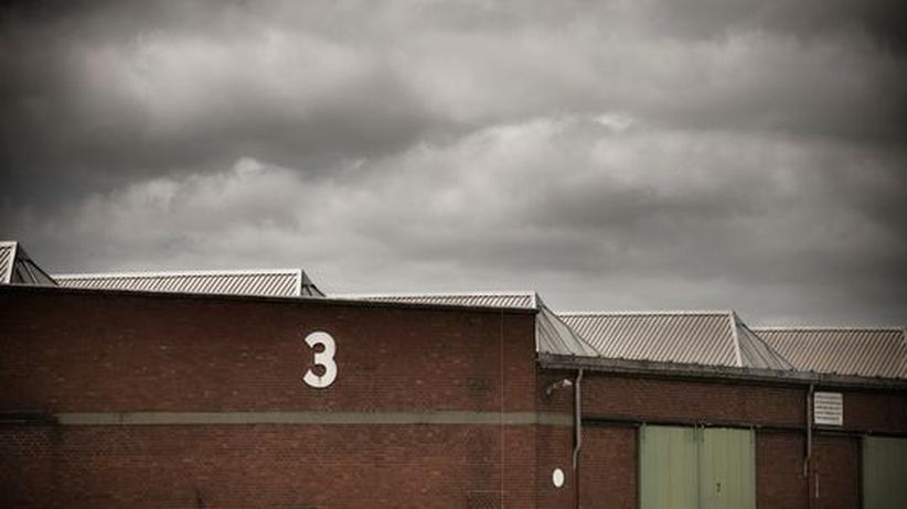 Dunkle Wolken über einer Lagerhalle im Hamburger Hafen
