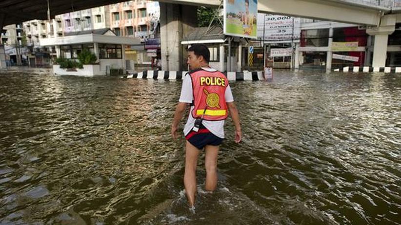 Erderwärmung: Ein Polizist watet durch das Hochwasser in Bangkok.