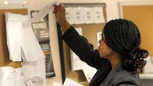 Eine Arbeitssuchende schaut in New York über eine Liste, auf der Jobangebote stehen.