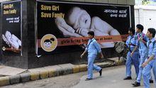 Indische Schuljungen vor einer Anzeigetafel in Neu Delhi, die für die Geburt von Mädchen wirbt