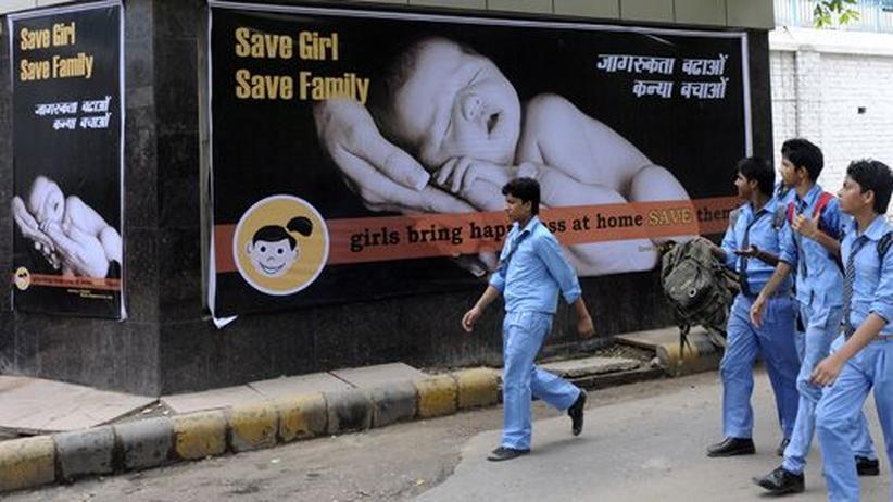 Indien: Indische Schuljungen vor einer Anzeigetafel in Neu Delhi, die für die Geburt von Mädchen wirbt