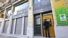 Ein Mann steht an einem Geldautomaten in Athen.