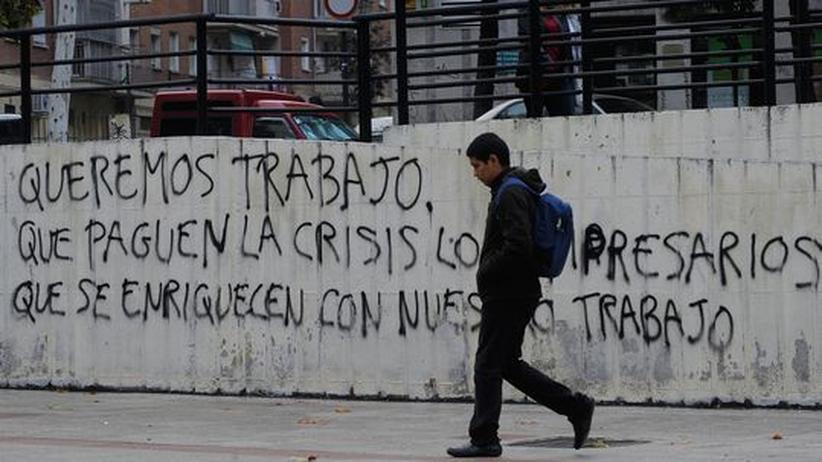 """Jugendarbeitslosigkeit: Ein Passant im vergangenen November vor einem Graffito in Madrid: """"Wir wollen arbeiten. Die Krise sollen die Unternehmer bezahlen, die durch unsere Arbeit reich geworden sind."""""""