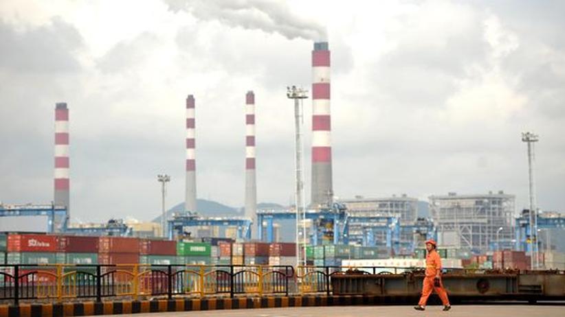 Weltwirtschaft: Ein Arbeiter vor Containern im Ningbo-Zhoushan-Hafen an der Ostküste Chinas