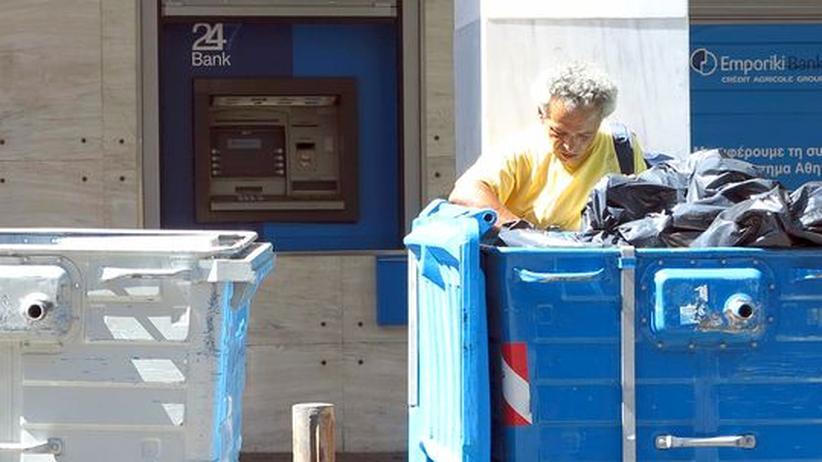 Ein Mann sucht nach Essbarem in einem Müllcontainer in Athen.