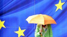 Eine Frau geht an einer Flagge der Europäischen Union vorbei.