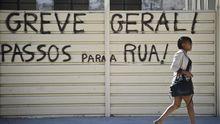 Eine Passantin in Lissabon vor einem Graffito, das zum Generalstreik aufruft