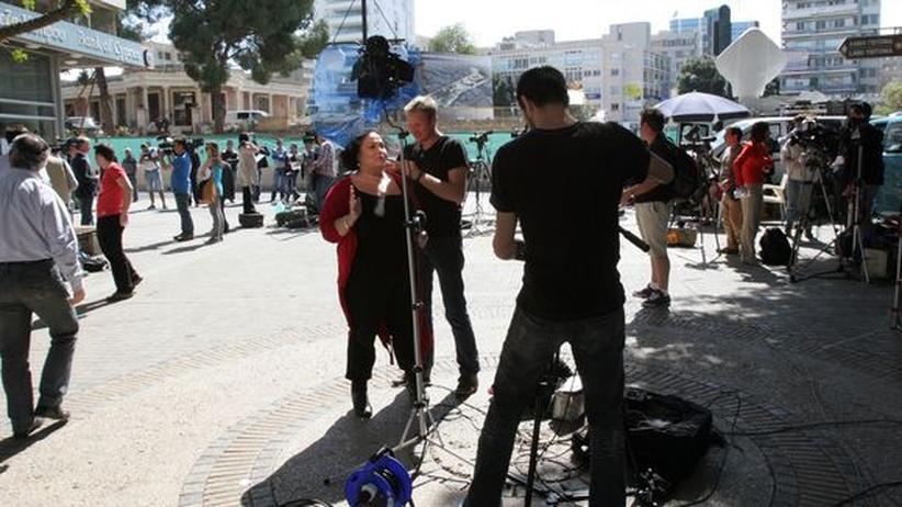 Journalisten stehen vor einem Gebäude der Bank of Cyprus. Viele bereiten Schalten für ihre Sender im Ausland vor.