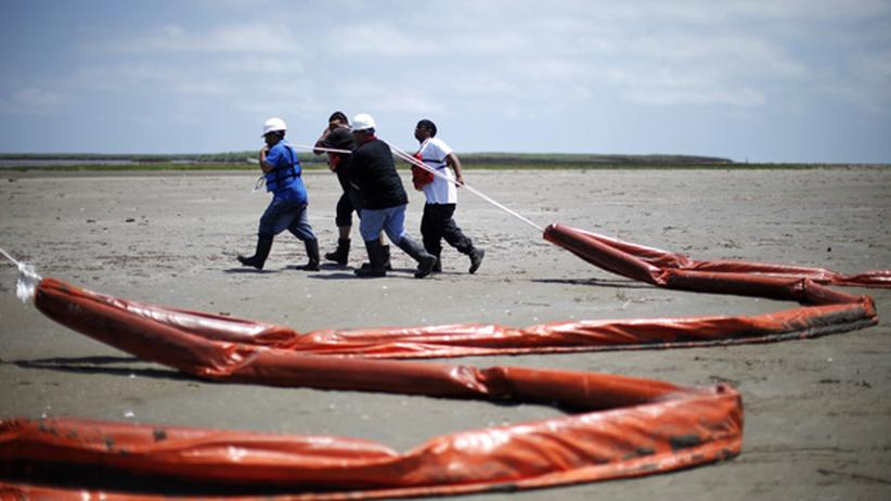 """US-Ölpest: Mai 2010: Südlich von Venice (Louisiana) ziehen Arbeiter nach dem Unglück der """"Deepwater Horizon"""" Ölbarrieren über den Strand."""