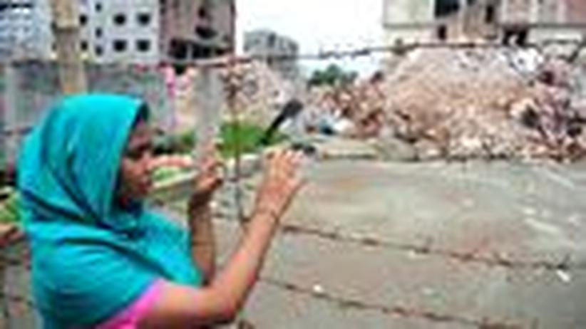 Unfair Trade: Nasima Akter, eine der Näherinnen von Rana Plaza, vor der Fabrikruine in Bangladesch