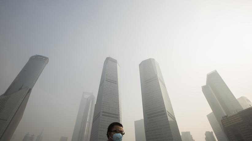 Eine Chinese mit einer Atemmaske im Finanzdistrikt von Shanghai
