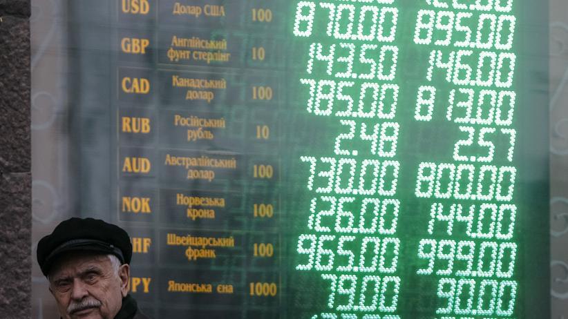 Ein Rentner in Kiew vor einer Anzeigetafel für Wechselkurse