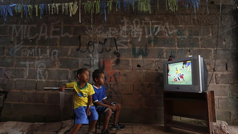 Das Geschäft mit dem Fußball: In einem Slum im Vorort von Brasilia gucken zwei Jungen das Vorrundenspiel zwischen Brasilien und Mexiko, Juni 2014.