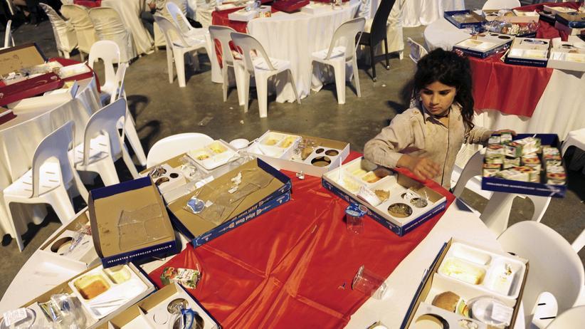 Welthungerbericht : Ein Mädchen, das aus Syrien geflohen ist, sammelt Essen ein – fotografiert im vergangenen Juli während des Ramadans in Istanbul, nach einem öffentlichen Fastenbrechen.