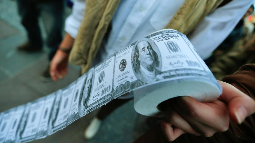 OECD-Studie: A demonstrator holds toilet paper made from fake U.S. dollars during a protest against Turkey's Prime Minister Tayyip Erdogan and his ruling Ak Party (AKP) government in Ankara February 27, 2014.