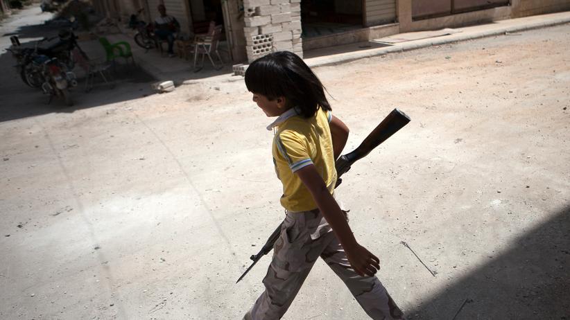 Ein Junge mit Waffe in der Hand läuft durch eine Stadt in Syrien (Archiv)