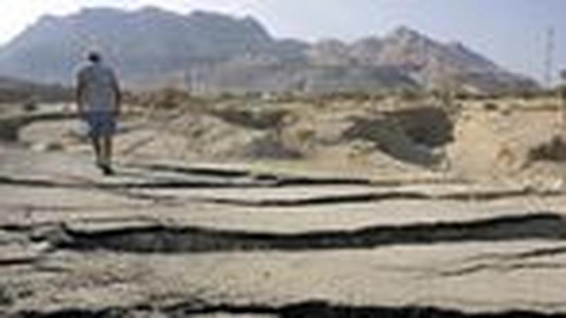 Ein Mann geht an Kratern vorbei, die sich in der Nähe des Kibbuz En Gedi im Jordantal im Boden aufgetan haben. (Archivbild)