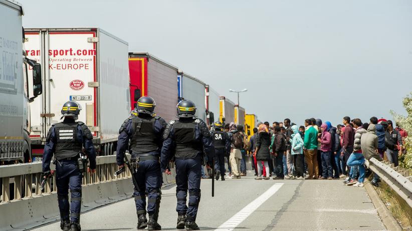 Flüchtlinge: Französische Polizisten und Flüchtlinge am Eingang zum Eurotunnel in Calais