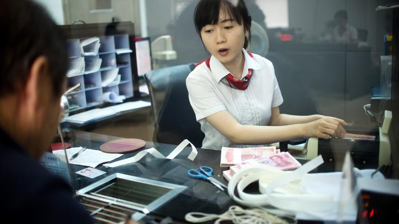 China: Eine Bankangestellte in Shanghai bedient am Schalter einen Kunden (Archivbild).