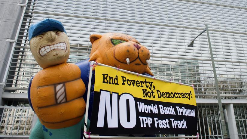 """Schiedsgerichte: """"Beendet die Armut, nicht die Demokratie!"""" Demonstranten protestieren vor dem Gebäude der Weltbank in Washington gegen das Schiedsgerichtsverfahren von Pacific Rim versus El Salvador (Archiv)."""
