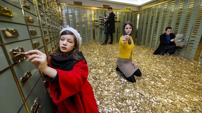 Phishing: Im Safe einer Schweizer Bank, auf einem Berg goldener Münzen, demonstrierten Aktivisten im Dezember 2013 für ein Grundeinkommen. Mit ihm wäre die Frage, wie man sein Geld am besten fürs Alter anlegt, womöglich leichter zu beantworten.
