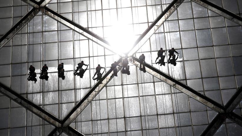 Weltwirtschaftsbericht: Arbeiter reinigen die Fenster eines Gebäudes in einem Pekinger Geschäftsviertel.