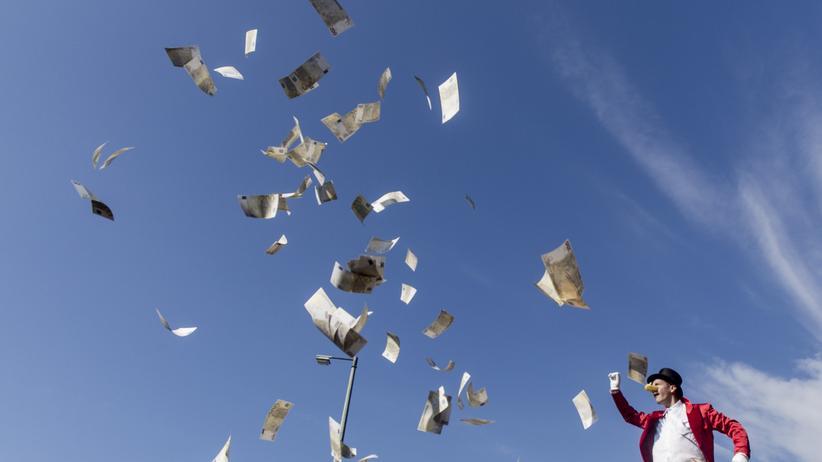 Wirtschaftsforschung: Reiche sollen mehr abgeben: Ein als Dagobert Duck verkleideter Aktivist wirft auf einer Demonstration in Berlin Spielgeld in die Luft (Archivbild).