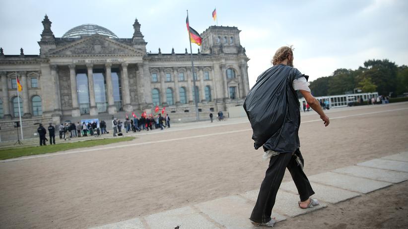 Vermögen: Ein offenbar obdachloser Mann vor dem Bundestag in Berlin (Archivbild)